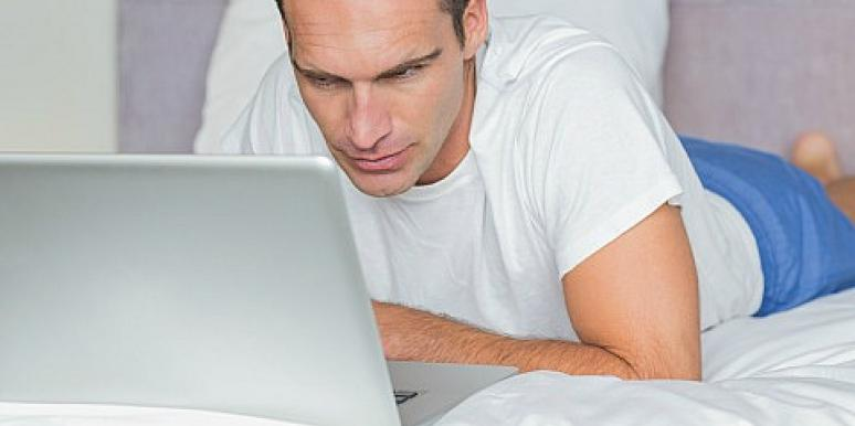 man looking at laptop in bed