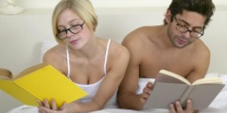 Couple wearing glasses and reading in bed
