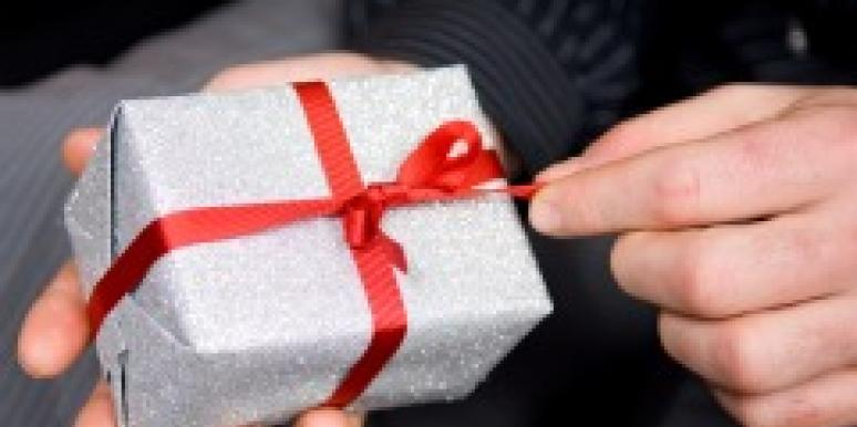 Man's hand opening a Christmas gift