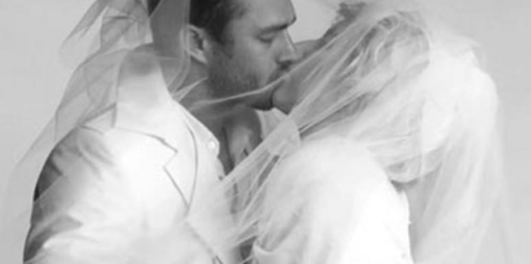 Taylor Kinney and Lady Gaga, rumored to be engaged, kiss under a veil in a black and white wedding-themed photo