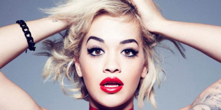 Rita Ora, from the shoulders up, wearing black eyeliner and red lipstick in a Rimmel ad
