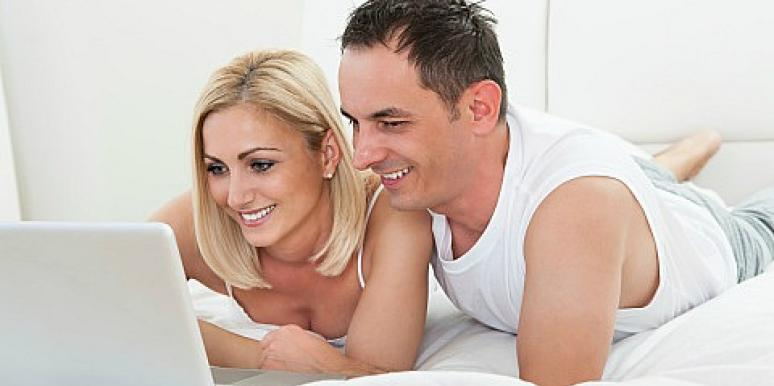 man and woman looking at laptop in bed