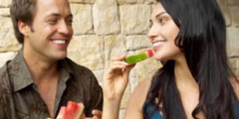 man and woman eating a watermelon