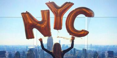 girl holding nyc sign