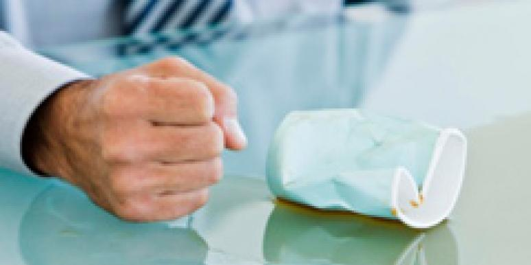 angry man's fist on table with a spill and a crushed paper cup