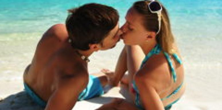 couple kissing swimsuits on beach