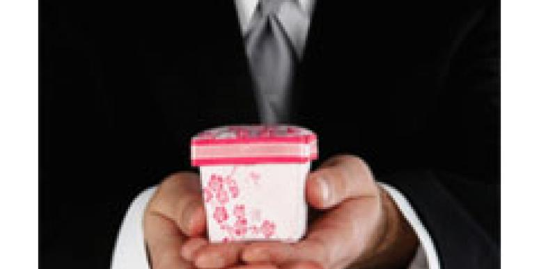 man in suit presenting small gift box