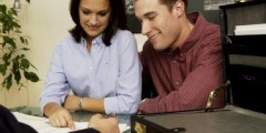Man and woman signing papers in an offce