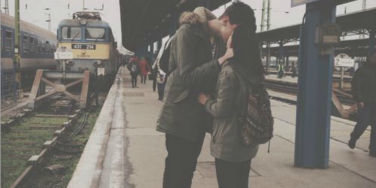 couple kissing next to train