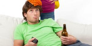 woman standing over man with beer and remote
