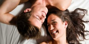 couple smiling in bed.