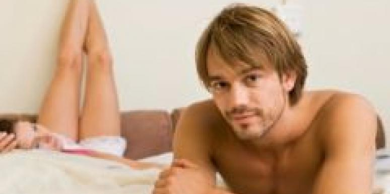 white couple relaxing in bed man in forefront woman legs raised