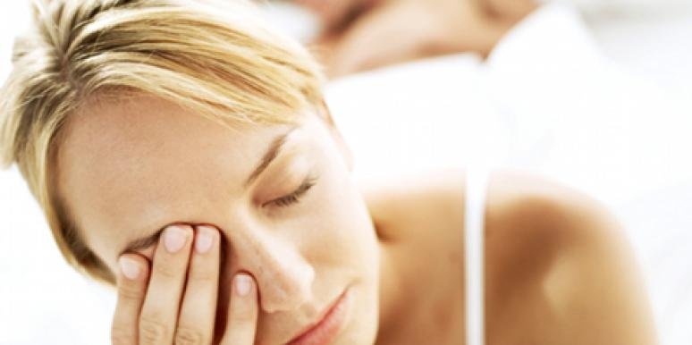 tired woman rubbing eyes in bed