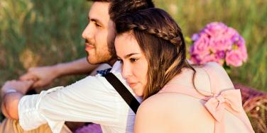 young couple smiling and gazing into the distance.
