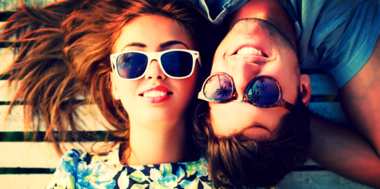 Guy and girl in sunglasses laying down