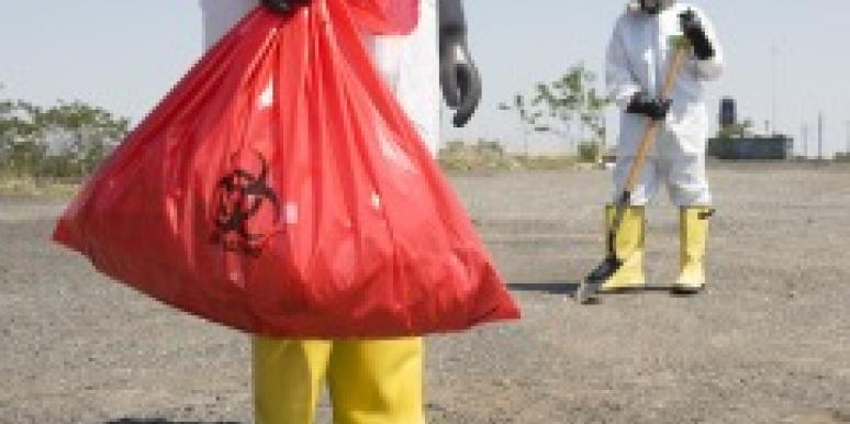 Workers in protective suits disposing of hazardous waste