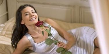 Woman with a rose lying on a bed