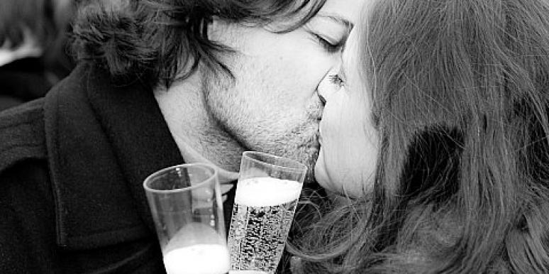 a couple kissing with champagne