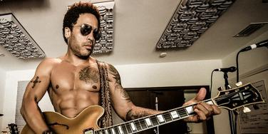Lenny Kravitz playing guitar shirtless in a bedroom studio from his Instagram page