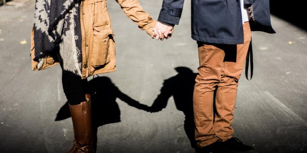 Couple holding hands while woman turns away