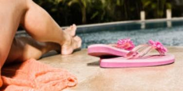 woman poolside lounging flip flops legs