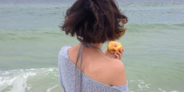 Woman looking out at the ocean eating a peach.