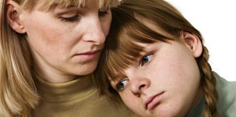 sad daughter leaning on mother's shoulder