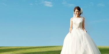 woman walking in field in wedding dress