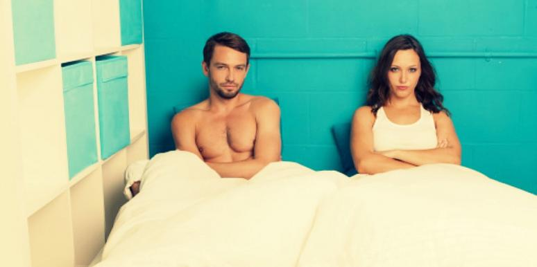 couple in bed unhappy