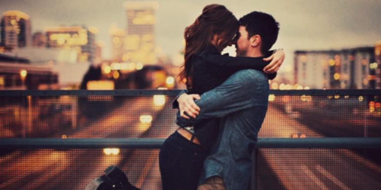 couple hugging in front of city backdrop