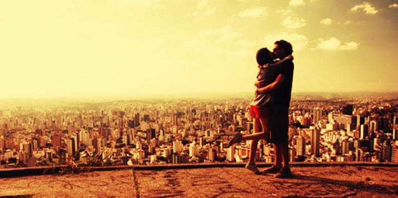couple kissing in front of skyline