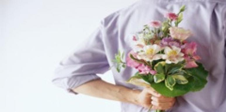 man holding flowers behind back