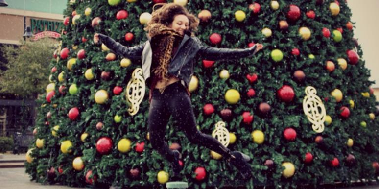 girl jumping in front of christmas tree