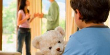 parents fighting in front of son holding teddy bear