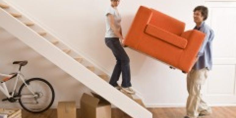 Couple carrying a couch upstairs