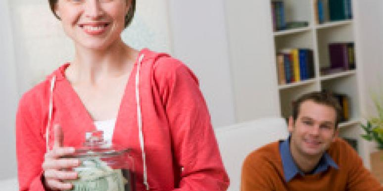 smiling couple with savings jar