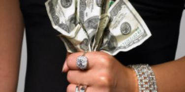 woman holding cash in her fist