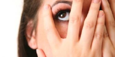 woman covering face with hands looking up