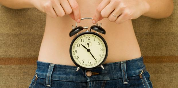 clock over woman's stomach