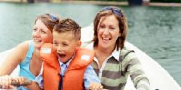 two women with young boy in rowboat