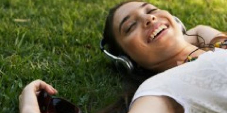 happy woman lying in grass listening to headphones
