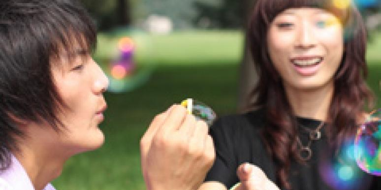 asian couple blowing bubbles outside