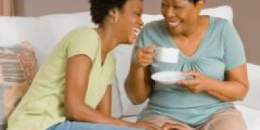 mother and daughter laughing on couch