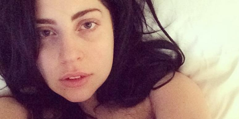 Lady Gaga with dark hair in bed wearing no makeup