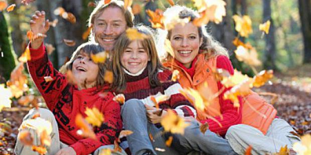 family playing in fall leaves outside