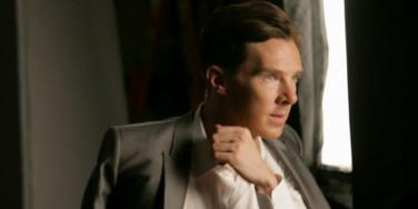 The newly engaged Benedict Cumberbatch wearing a grey and white suit, looking out a window