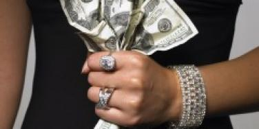Woman's hand clutching hundred dollar bills