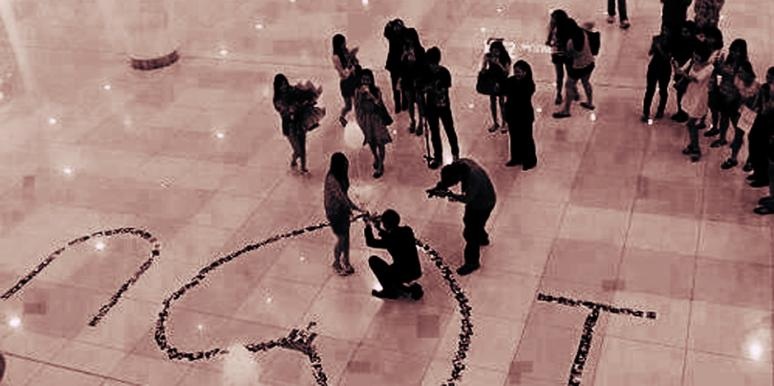 "A man gets down on one knee surrounded by rose petals spelling out ""I heart you"" to propose to his girlfriend that he loves and give her an engagement ring at a New Year's Eve party in front of her family and friends."