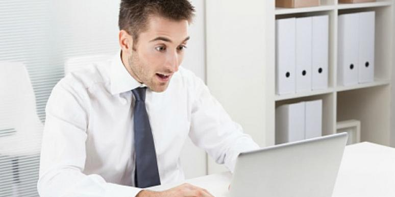 man looking shocked by his laptop