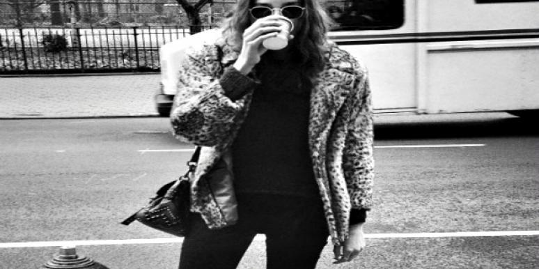 Woman drinking a hot beverage on the street.